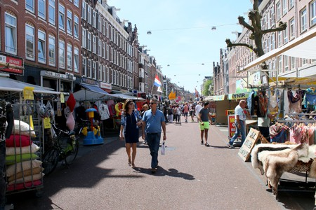 Street vendors and people shop at busy Albert Cuyp Market in the de Pijp borough