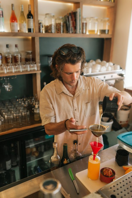 Bartender mixing cocktails behind a bar
