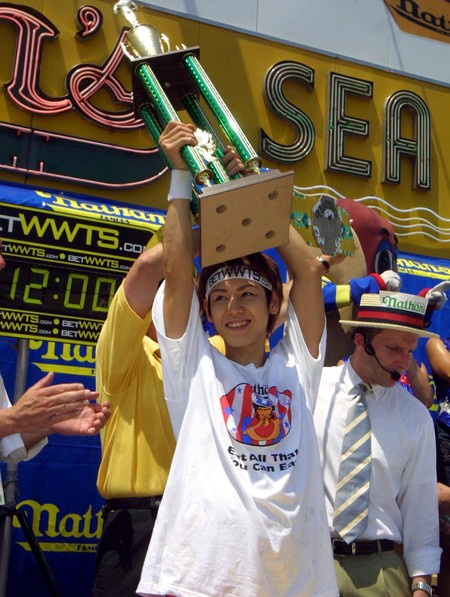 DEFENDING CHAMPION TAKERU KOBAYASHI WITH HIS TROPHY - HE BROKE HIS OWN RECORD BY EATING 50 AND A HALF HOT DOGS IN 12 MINUTES NATHANS ANNUAL 4TH OF JULY HOT DOG EATING CONTEST, NEW YORK, AMERICA