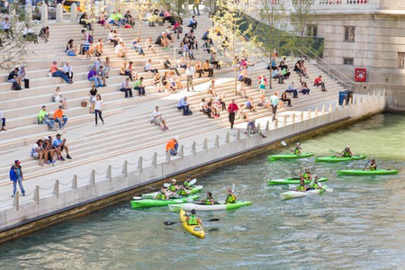 Kayakers on the Chicago River stop at the Riverwalk spot called the River Theater on a summers day in Chicago, Illinois, USA