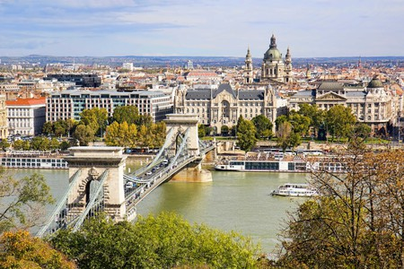 Chain Bridge or Szechenyi Bridge across Danube river in Budapest, Hungary, with old buildings and dome of St Stephen's Basilica or Szent Istvan Bazili