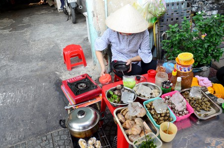 Woman cooking shell for sale on street