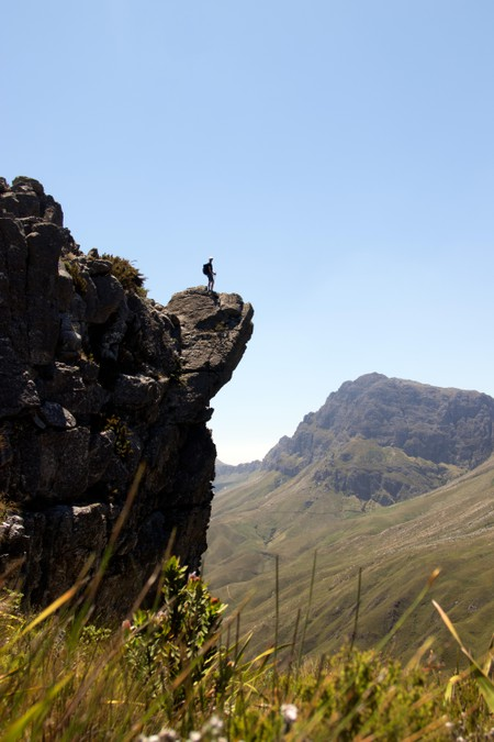 A man stands on the edge of a rock summit in the Jonkershoek nature reserve, Cape Town, South Africa.