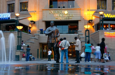 Tourists posing next to a statue of Nelson Mandela in Mandela Square in Sandton