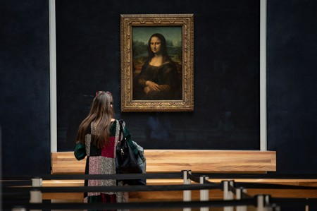 "A woman in front of Italian artist Leonardo da Vinci's ""Mona Lisa"" at the Louvre in Paris"