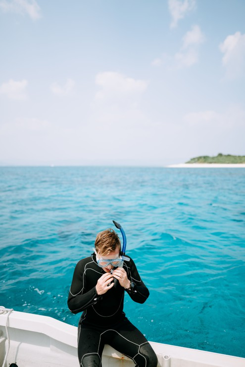 Man putting on snorkel mask on boat around tropical island with blue water, Okinawa, Japan