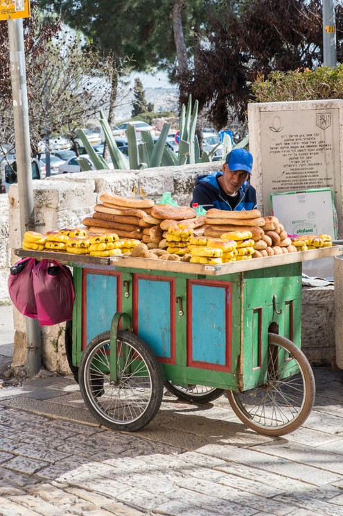 A street vendor pushs his bread cart through the streets of Jerusalem