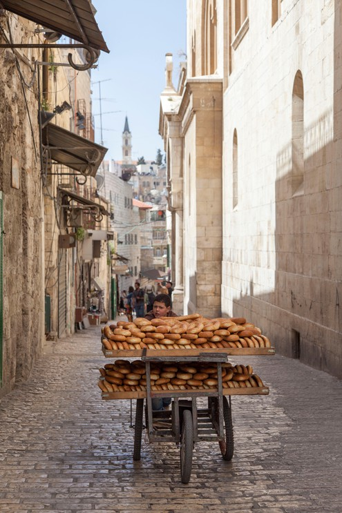 Boy pushing cart with bread along street in Jerusalem
