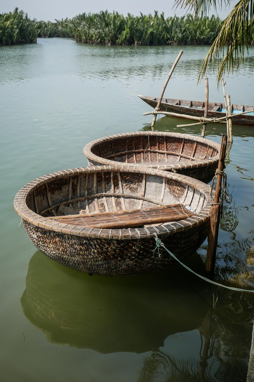 Coracle boats moored by a riverbank on Thu Bon river