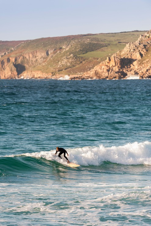 A lone surfer riding a wave at Sennen in Cornwall, England, UK