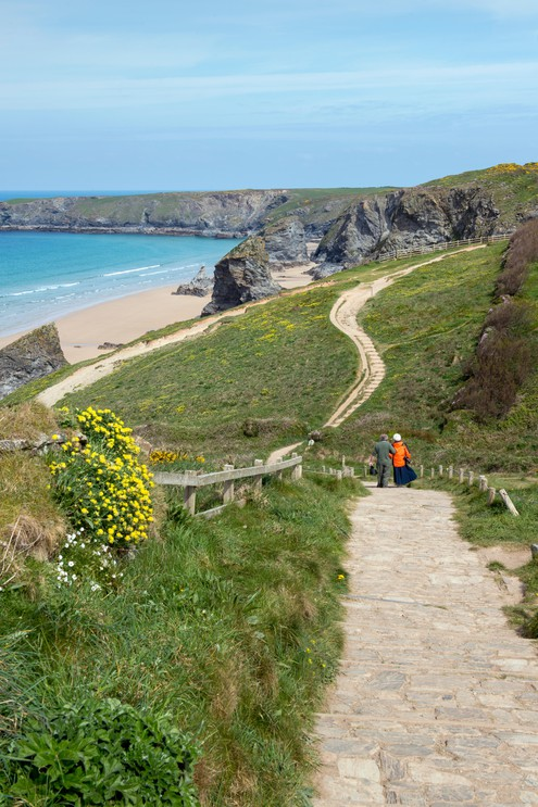 People walking on the South West Coast Path at Bedruthan Steps in Cornwall, England, UK