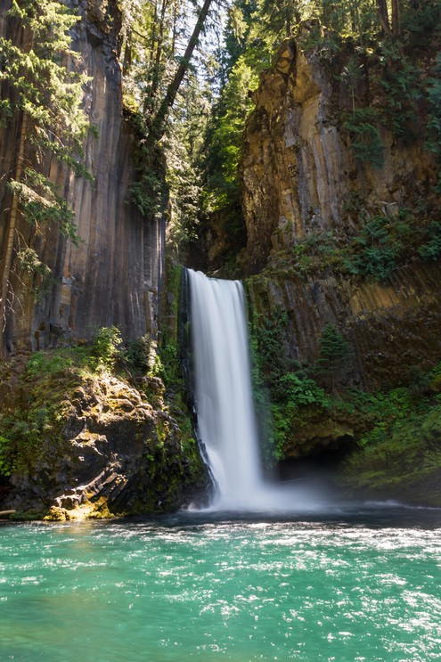 Beautiful Toketee Falls in Oregon, photo taken on a bright clear day with vivid colors
