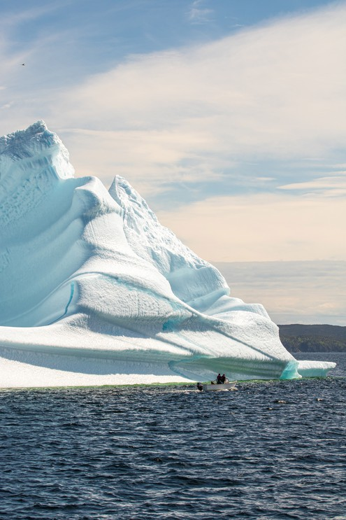 A small boat sailing next to a massive iceberg floating off the coast of Twillingate Newfoundland.