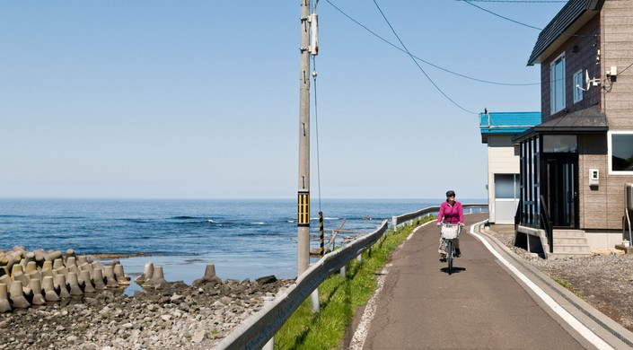 Woman riding a bicycle in Hokkaido, Japan