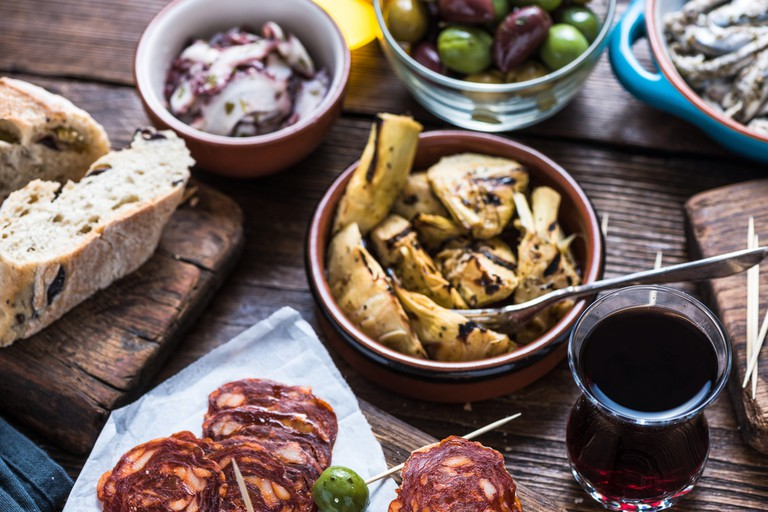 Sharing authentic spanish tapas with friends in restaurant or bar. © Merc67 / Shutterstock