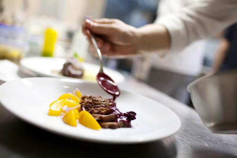 Chef is decorating delicious dish © Denizo71 / Shutterstock