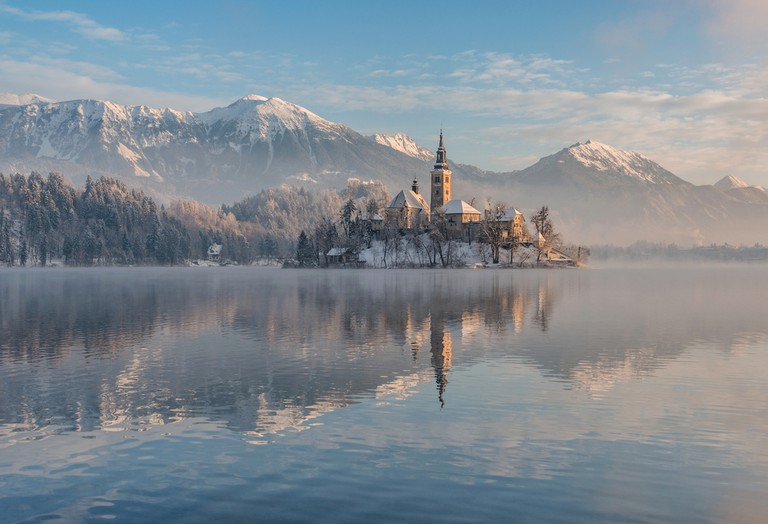 Lake Bled with the church and the castle on a calm winter morning © Ales Krivec / Shutterstock