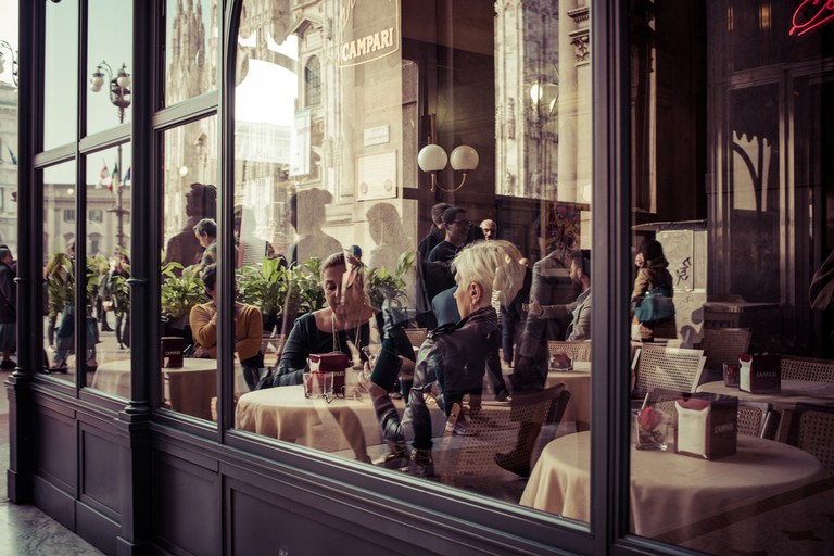 People eating at small cafe at Galleria Vittorio Emanuele II shopping mall in Milan ©Yulia Grigoryeva / Shutterstock