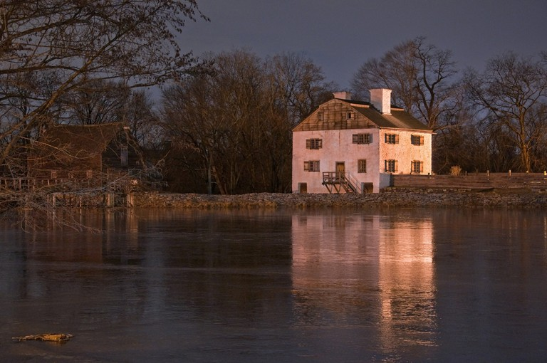 18th century Philipsburg Manor reflecting off the frozen pond. Sleepy Hollow NY