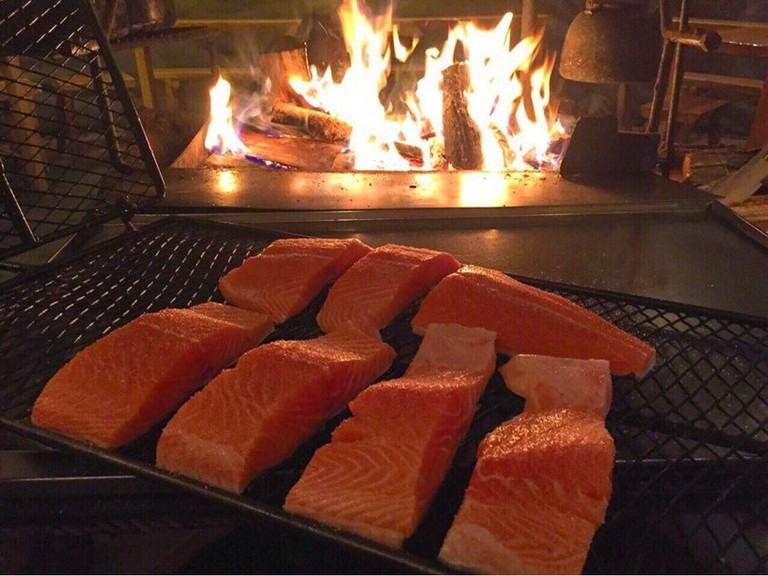 Fresh Salmon Going Into The Fire   Image Courtesy of Santa's Salmon Place