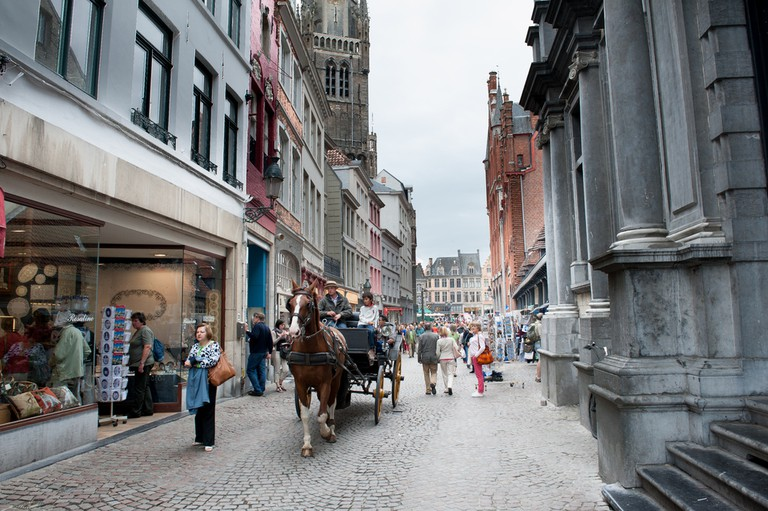 City street with people and typical horse cart walking around in daytime