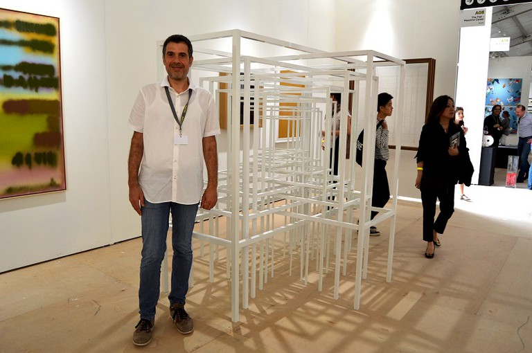Italian artist Paolo Cavinato stands beside his new work titled Protection #2, 2015 [Varnished aluminum, 86 3/5 × 118 1/10 × 107 1/10 in, 220 × 300 × 272 cm] at The Flat - Massimo Carasi (Milan ) booth. | © Lisa Morales