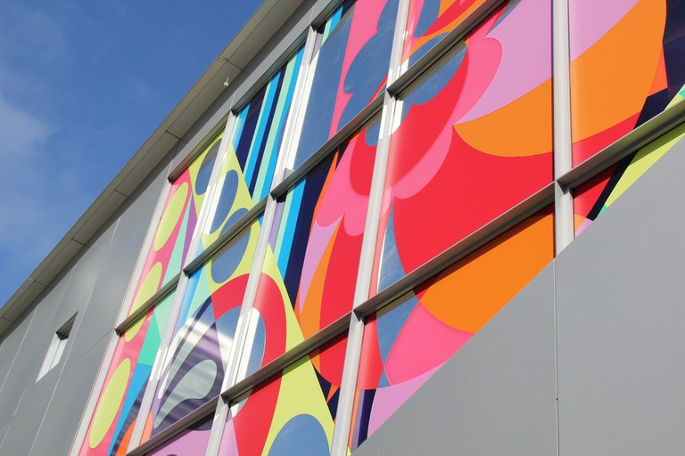Art lined windows on one wall of the center © daveynin