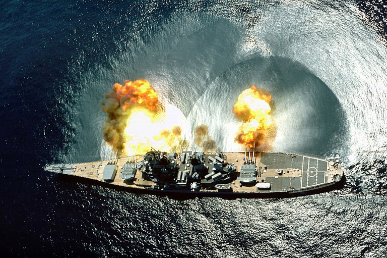 Iowa fires a full broadside of nine 16-inch (410 mm)/50-caliber and six 5-inch (130 mm)/38 cal guns during a target exercise near Vieques Island, Puerto Rico, on 1 July 1984. Shock waves are visible in the water @ Phan J. Alan Elliott/Wikipedia