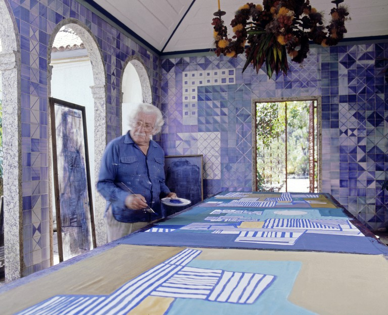 Roberto Burle Marx painting a tablecloth in the loggia of his home, 1980s; the azulejo tile walls and chandelier composed of fruit and flowers on a metal armature are his work. | © Tyba