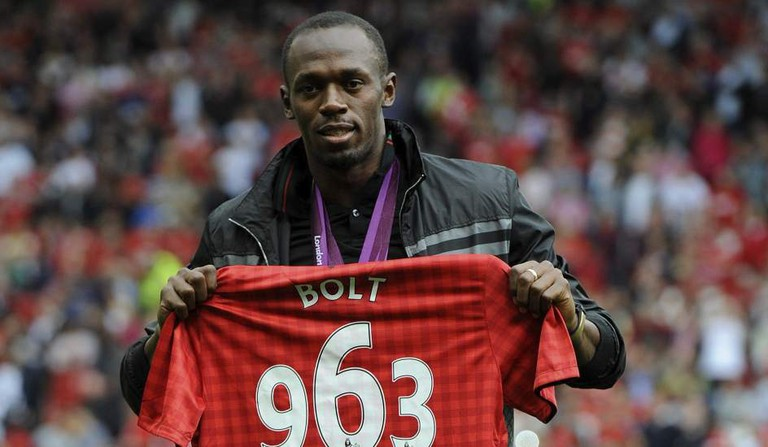 Usain Bolt holds up a Manchester United jersey with 963 on it, honoring his gold-medal winning time at the 2012 Olympics | © Flickr