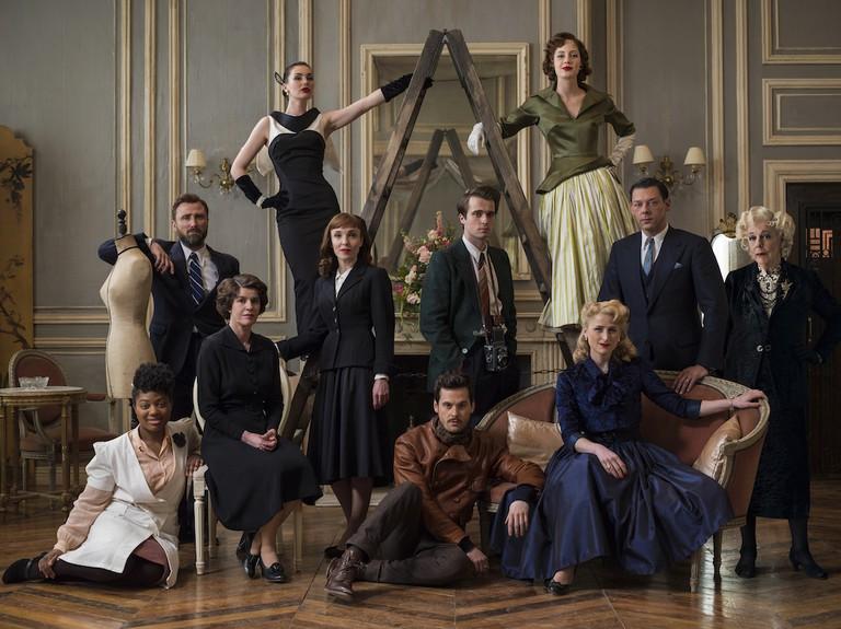 The Collection, Amazon Prime Video (L-R) Juliette (BETHAN MARY-JAMES), Victor Bastide (ALEXANDRE BRASSEUR), Marianne (IRENE JACOB), Dominique (POPPY CORBY-TUECH), Charlotte (ALIX POISSON), Claude Sabine (TOM RILEY) seated on floor, Billy Novak (MAX DEACON), Nina (JENNA THIAM) on ladder, HELEN SABINE (MAMIE GUMMER), Paul Sabine (RICHARD COYLE), and Yvette Sabine (FRANCES DE LA TOUR)