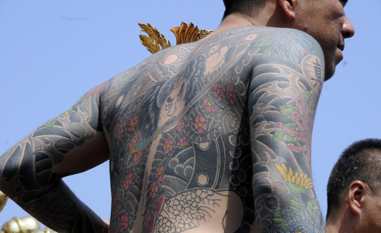 A man with yakuza-style tattoos at a festival