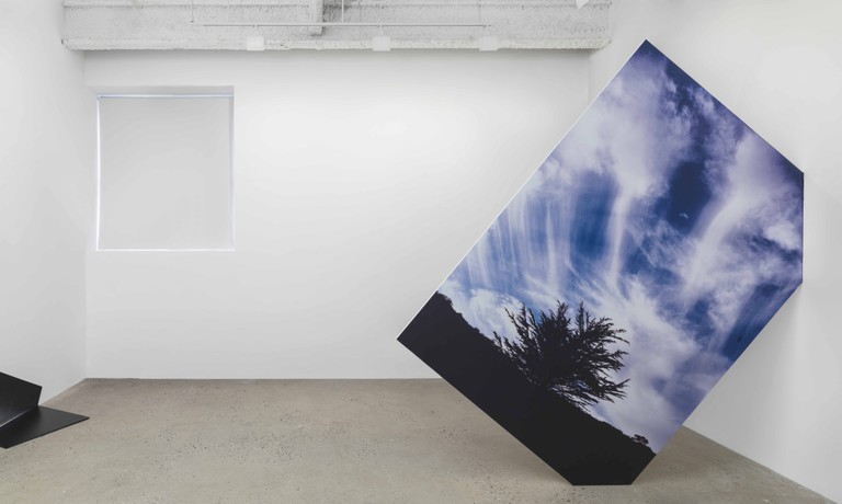 Installation view, Solo exhibition at Higher Pictures, 2014 Skyfall Wallbreak California, 2014 UV print on dibond, wood, hole in wall 96 x 96 x 7/8 inches | Courtesy of Letha Wilson