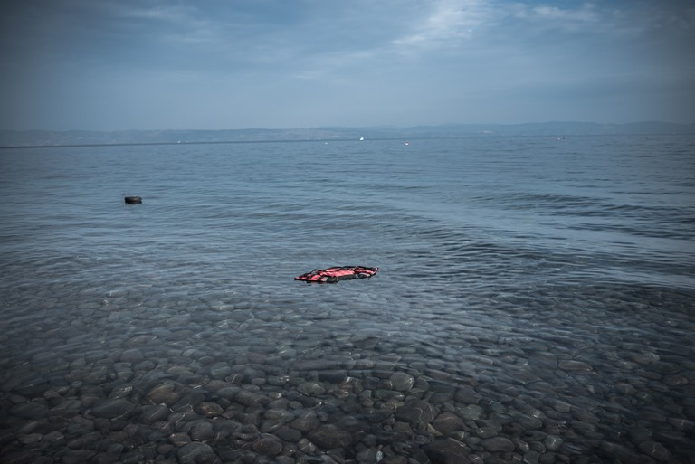 A plastic lifejacket floating near the shore after a dinghy arrived with refugees and migrants on the Greek island of Lesbos after crossing the Aegean sea from Turkey on October 21, 2015. © Orestis Seferoglou