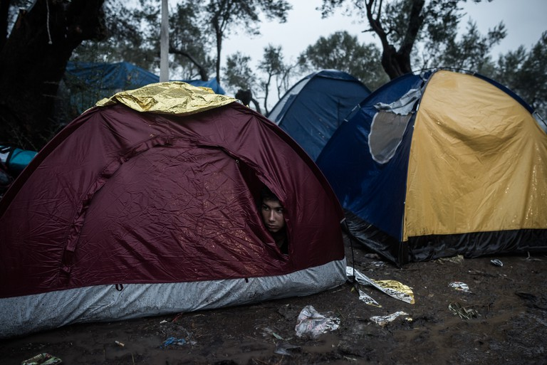 A migrant takes shelter from the heavy rain inside his tent, outside the Moria registration camp, on October 23, 2015, on the Lesbos island. Over 400,000 people have landed on Greek islands from neighbouring Turkey since the beginning of the year, most of them fleeing the civil war in Syria. © Orestis Seferoglou