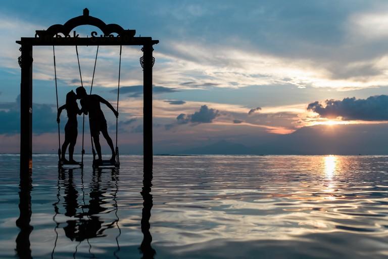 Couple on Gili Trawangan swing in Indonesia © Azrul Aziz/Unsplash