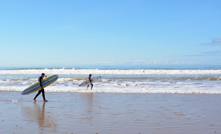 Sidi Kaouki, Morocco - January 7, 2016: Two surfers carrying a surfboard on the beach near Essaouira © LukaKikina / Shutterstock