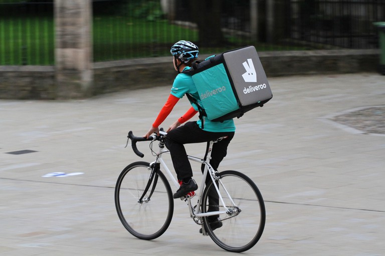 Deliveroo speeding through city streets with a hot food delivery from take aways and restaurants to homes © Nicholas Jackson / Shutterstock