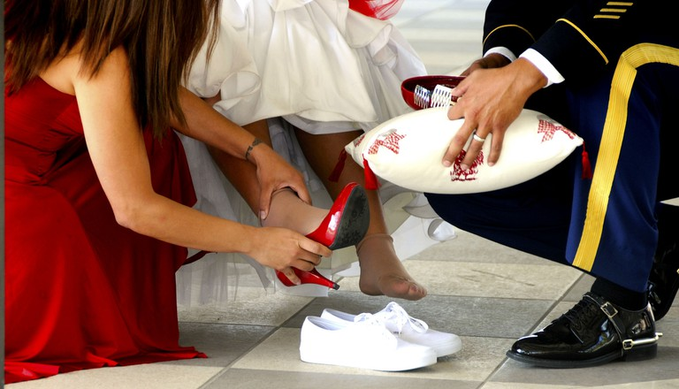 Changing her flats for heels during the quinceañera | © US Army Africa/Flickr