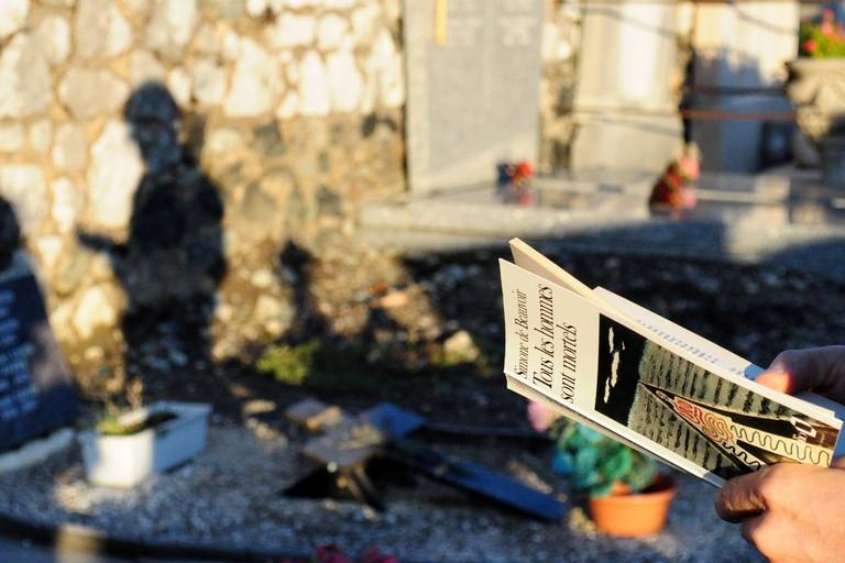 A pilgrim reading at the graveside of Jean-Paul Sartre and Simone de Beauvoir │© Frédérique Voisin-Demery