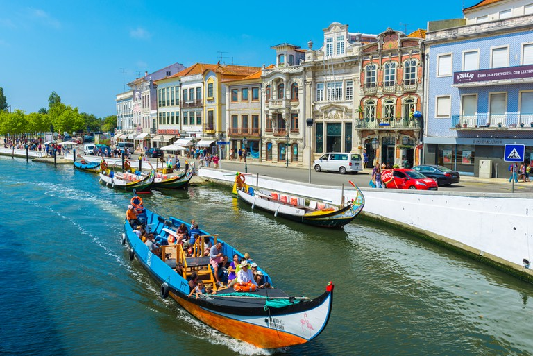 Moliceiro boats sail along the central canal in Aveiro, Portugal| ©Alberto Loyo/Shutterstock