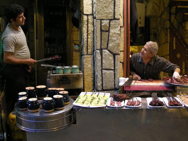 Vendors chat while skewering liver kabobs | © Pontia Fallahi