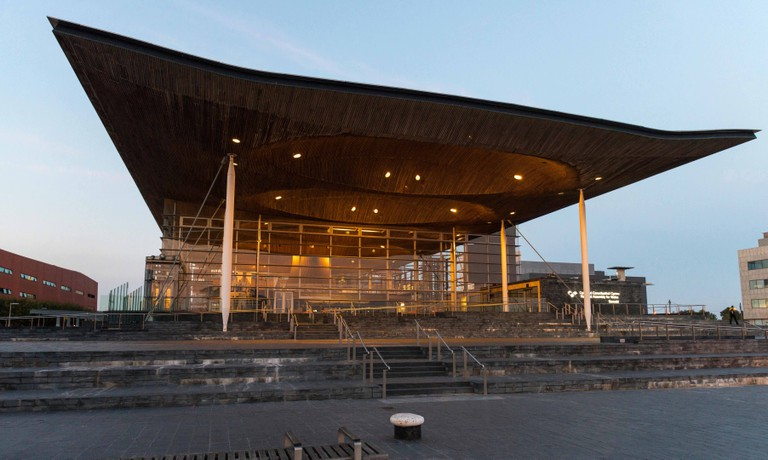 The lights glow in The Senedd, Cardiff Bay, South Wales, UK, as dusk settles over Cardiff Bay.Te