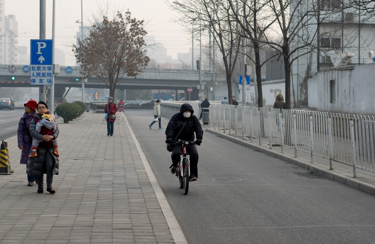 An unidentified man rides a bicycle during air pollution in Beijing| ©Nahorski Pavel/Shutterstock