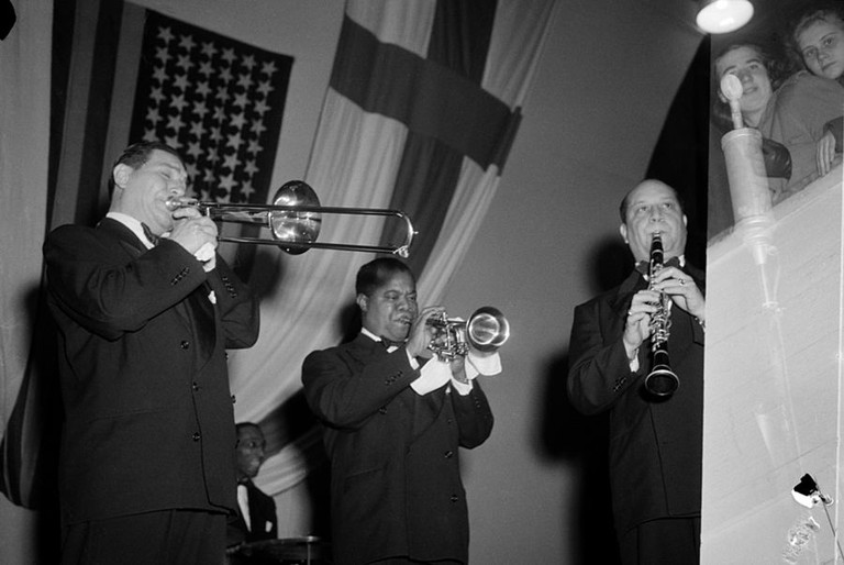 With Jack Teagarden (left) and Barney Bigard (right), Armstrong plays the trumpet in Helsinki, Finland/WikiCommons