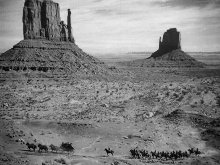 Travelers dwarfed by Monument Valley's East and West Mittens in 'Stagecoach' | © United Artists