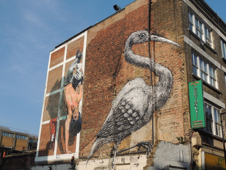 A large crane painted on the side of a buildingin Brick Lane