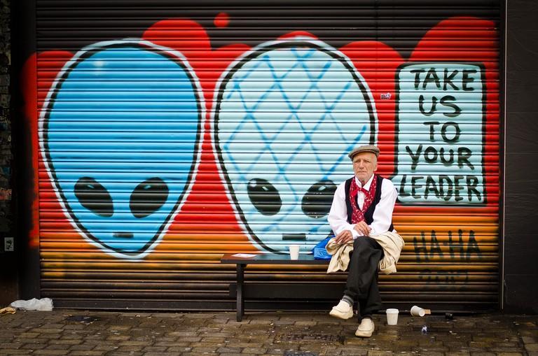 An old man sitting outside a street art mural