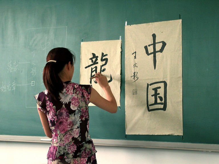 A woman writes the characters for 'China' and 'Dragon' | © Axel Rouvin/Flickr
