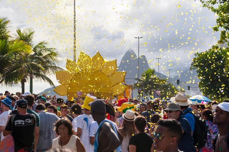 RIO DE JANEIRO, BRAZIL - FEBRUARY 07, 2015: Confetti flutters above crowd of Brazilians celebrating at a carnival street party.